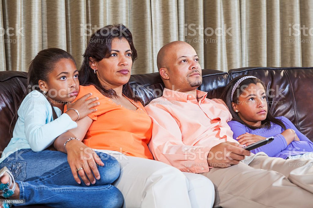 African American family watching TV, on sofa together stock photo