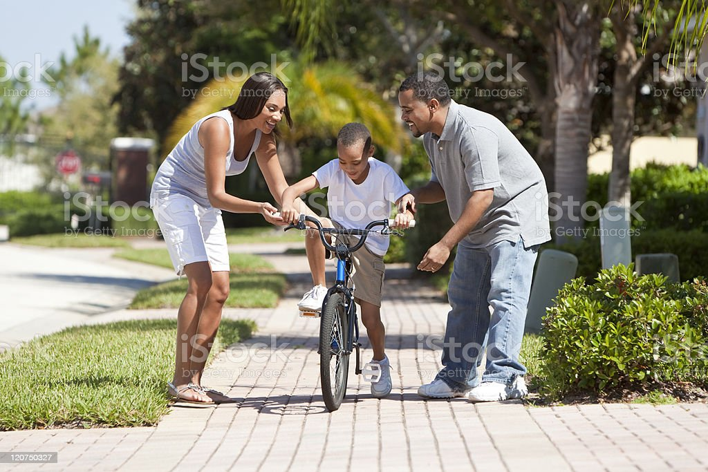 African American Family WIth Boy Riding Bike & Happy Parents royalty-free stock photo
