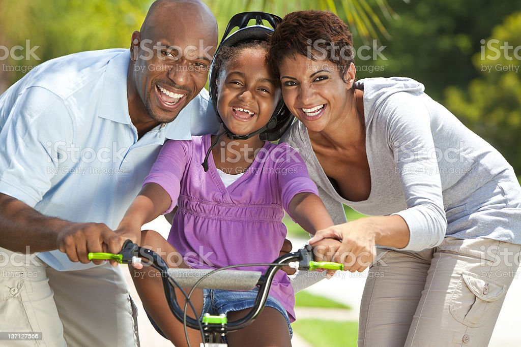 African American Family WIth Girl Riding Bike & Happy Parents royalty-free stock photo