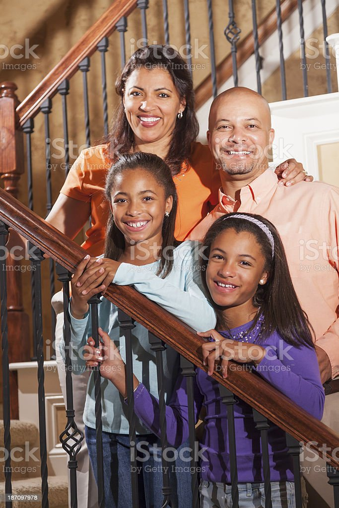 African American family with two children at home on staircase stock photo