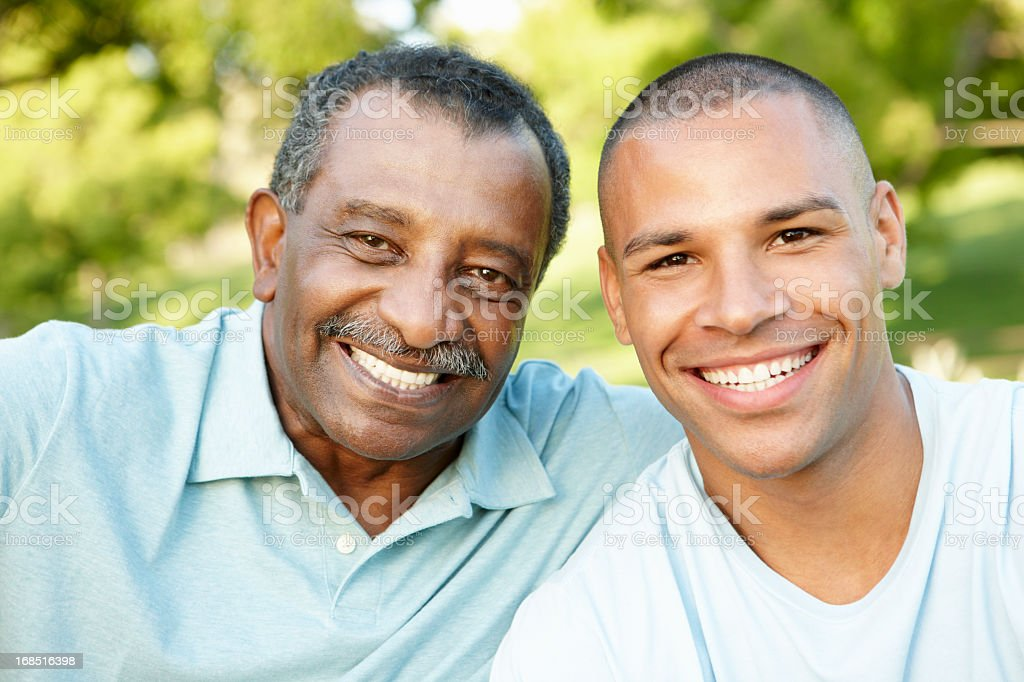African American Father And Adult Son Relaxing In Park stock photo