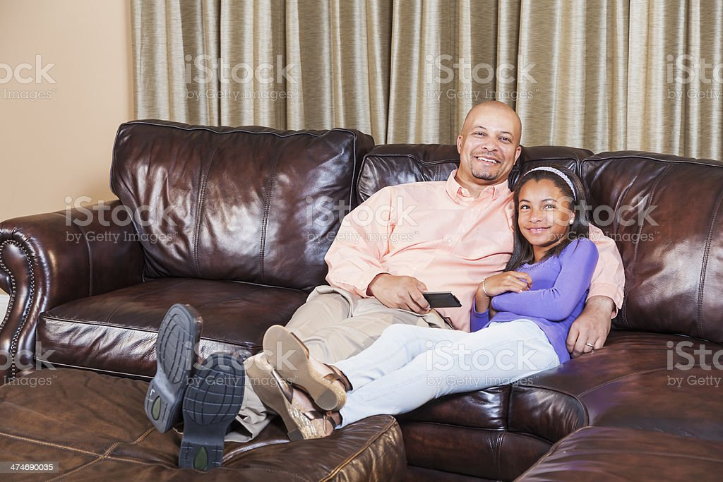 African American father and daughter watching television together on couch stock photo