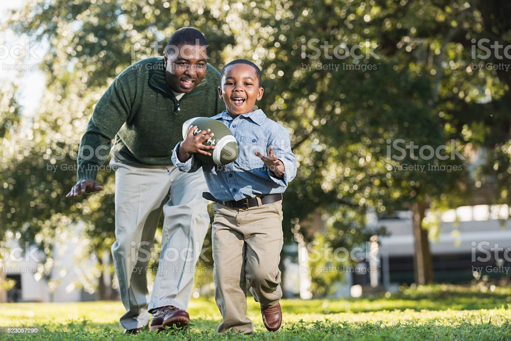African American father and son playing football stock photo