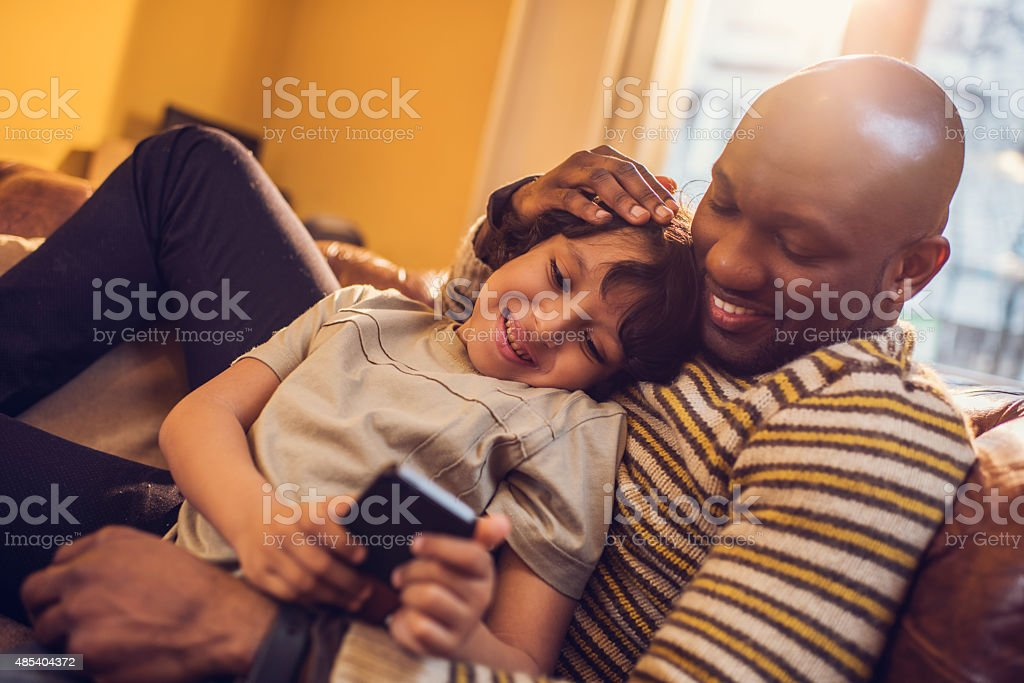 African American father and son text messaging on cell phone. stock photo