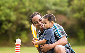 African American Father and Young Son outdoors playing T Ball