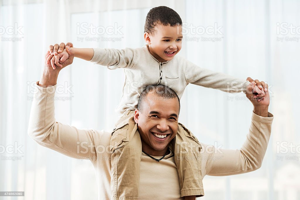 African American father carrying his son on shoulders at home. stock photo