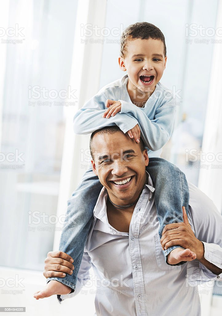 African American father carrying his son on shoulders. stock photo