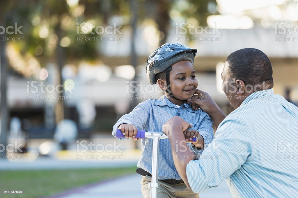 African American father helping boy on scooter stock photo