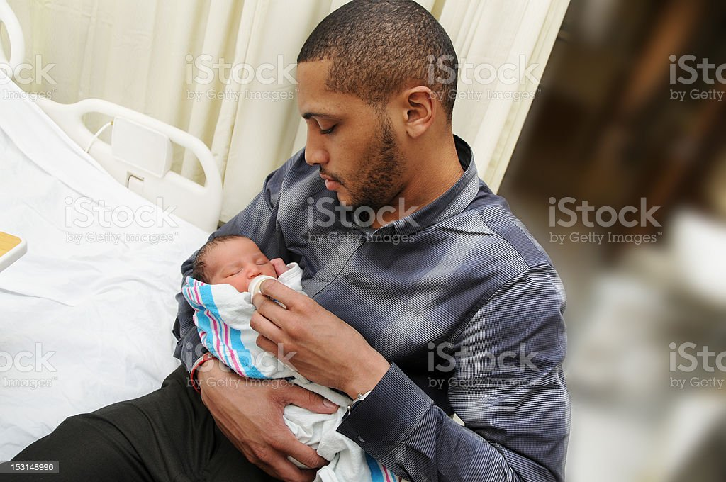 African American Father Holding and Feeding Newborn Infant Baby stock photo