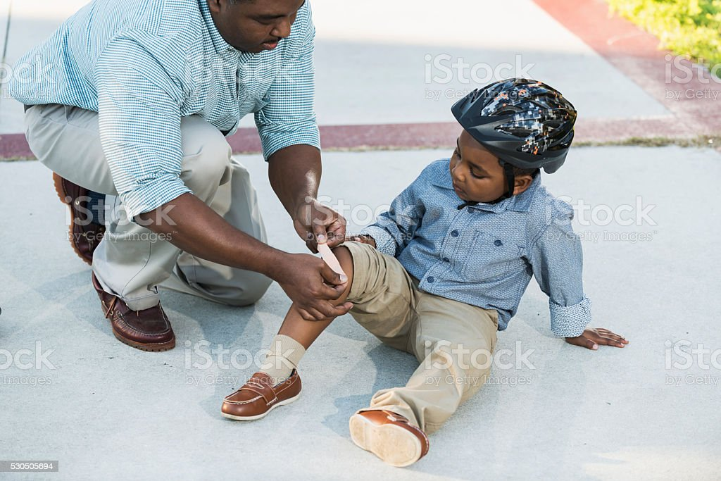 African American father putting bandage on son's knee stock photo