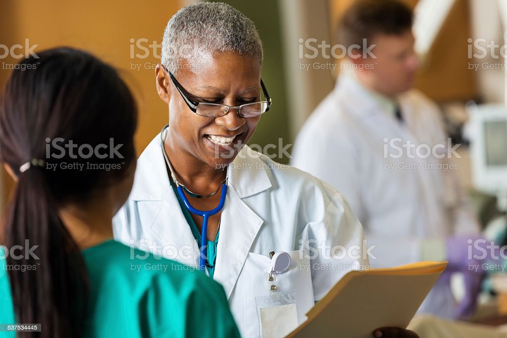 African American female doctor reading patient chart with hospital nurse stock photo