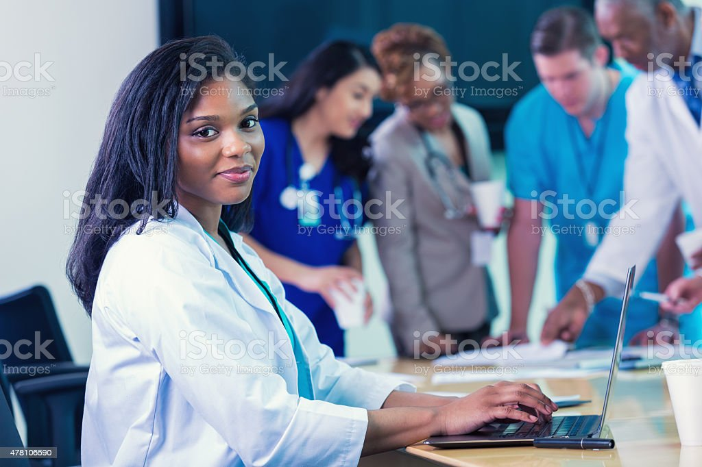 African American female doctor using laptop during hospital staff meeting stock photo
