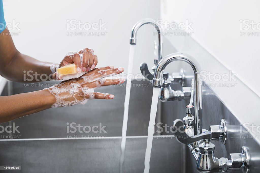 African American female surgeon washing hands stock photo