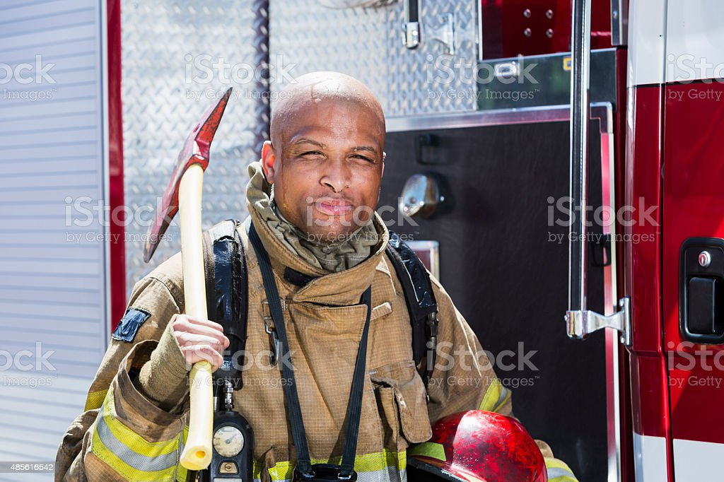 African American fire fighter carrying axe stock photo