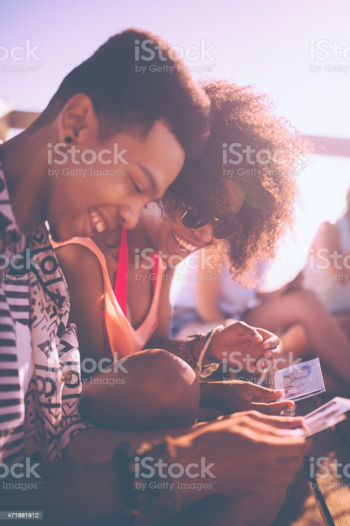 African American friends looking at photographs together at the beach stock photo
