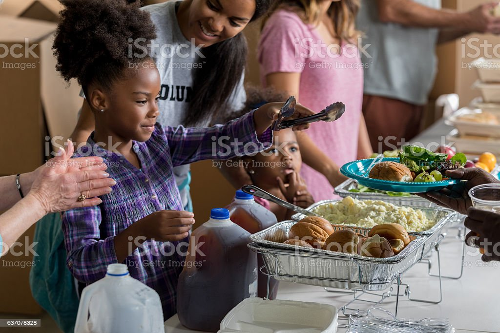 African American girl and family serve meals in soup kitchen stock photo