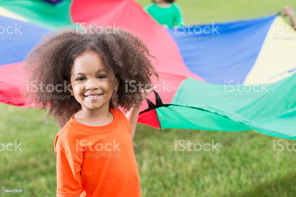 African American girl at summer camp holding parachute stock photo