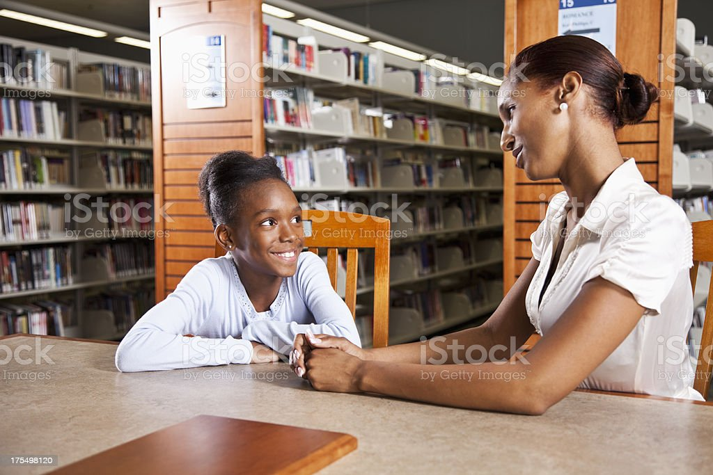 African American girl in library with teacher royalty-free stock photo