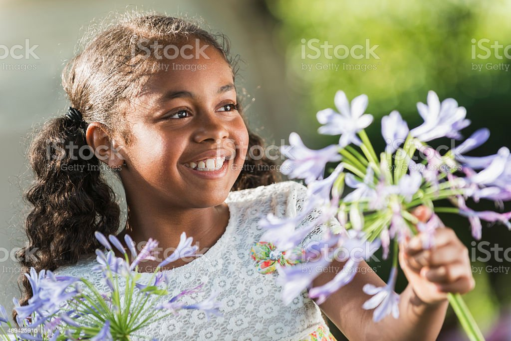 African American girl outdoors holding flowers stock photo