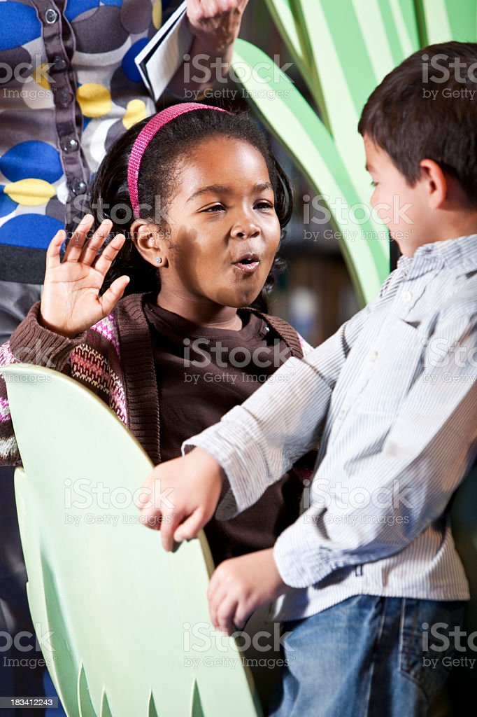 African American girl playing with classmate stock photo