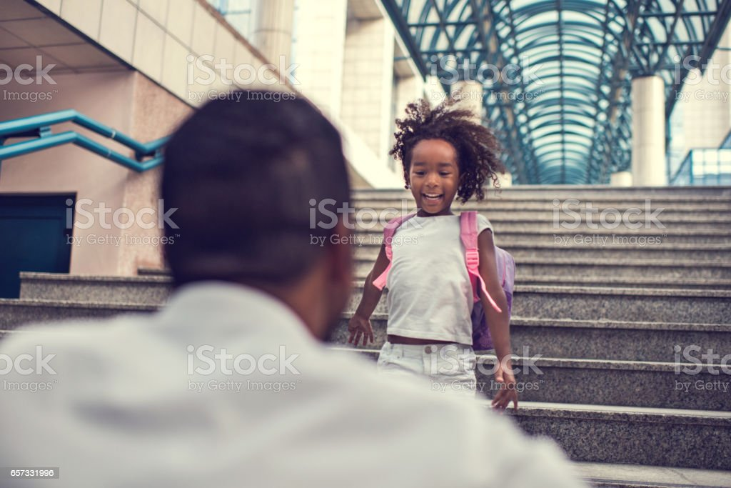 African American girl running down the stairs to her father. stock photo