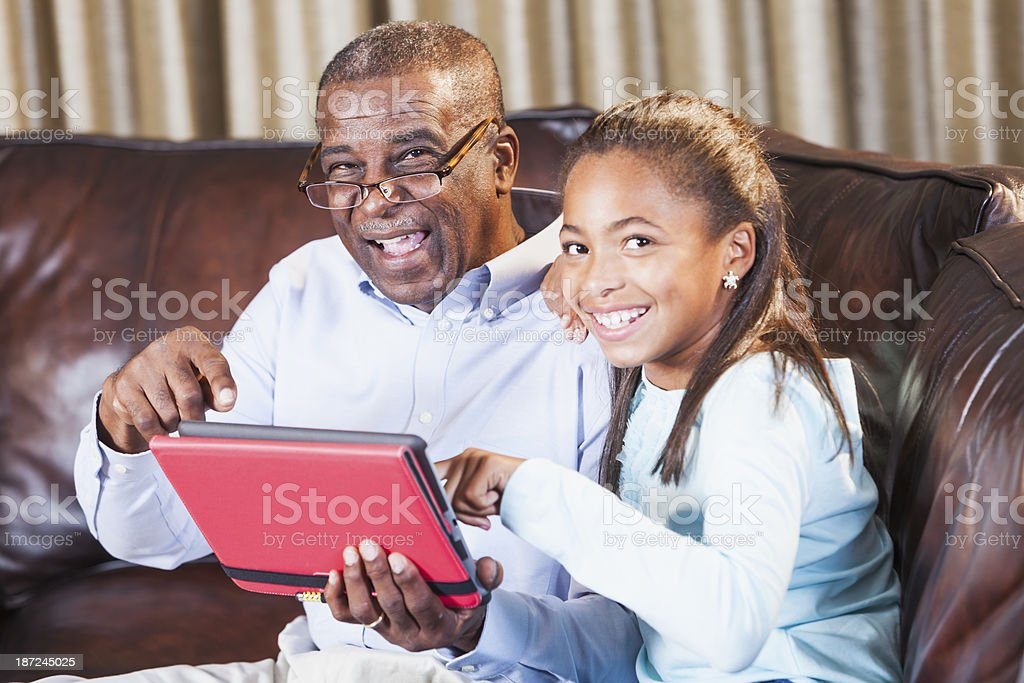 African American girl showing grandparent how to use digital tablet stock photo