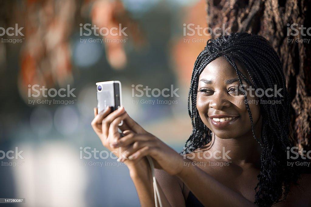 African American Girl taking photo in fall season stock photo