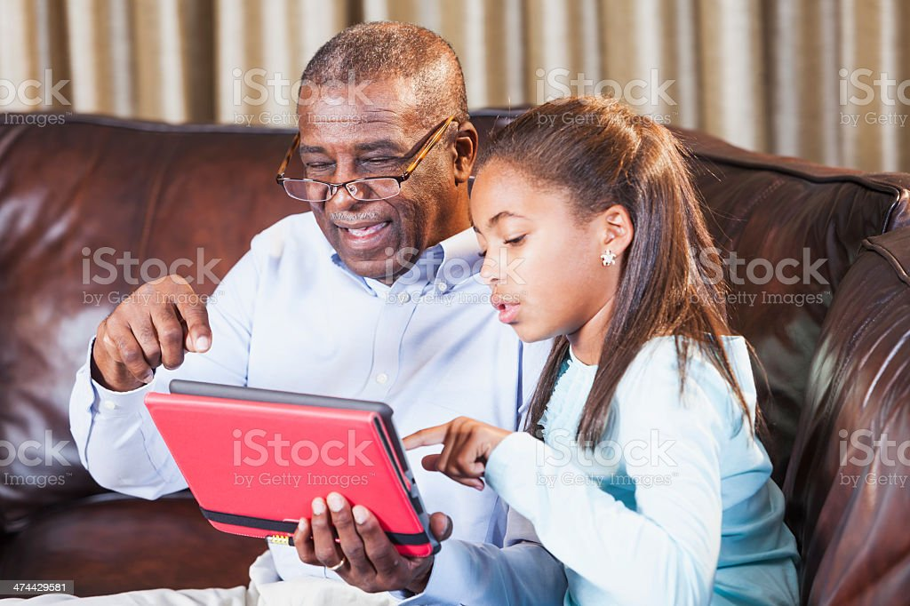 African American girl teaching grandfather to use digital tablet stock photo