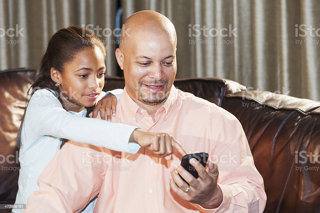 African American girl with father using smartphone stock photo
