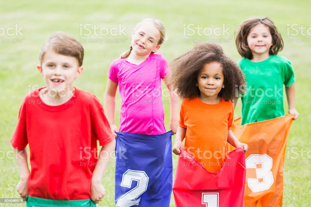 African American girl with friends in potato sack race stock photo