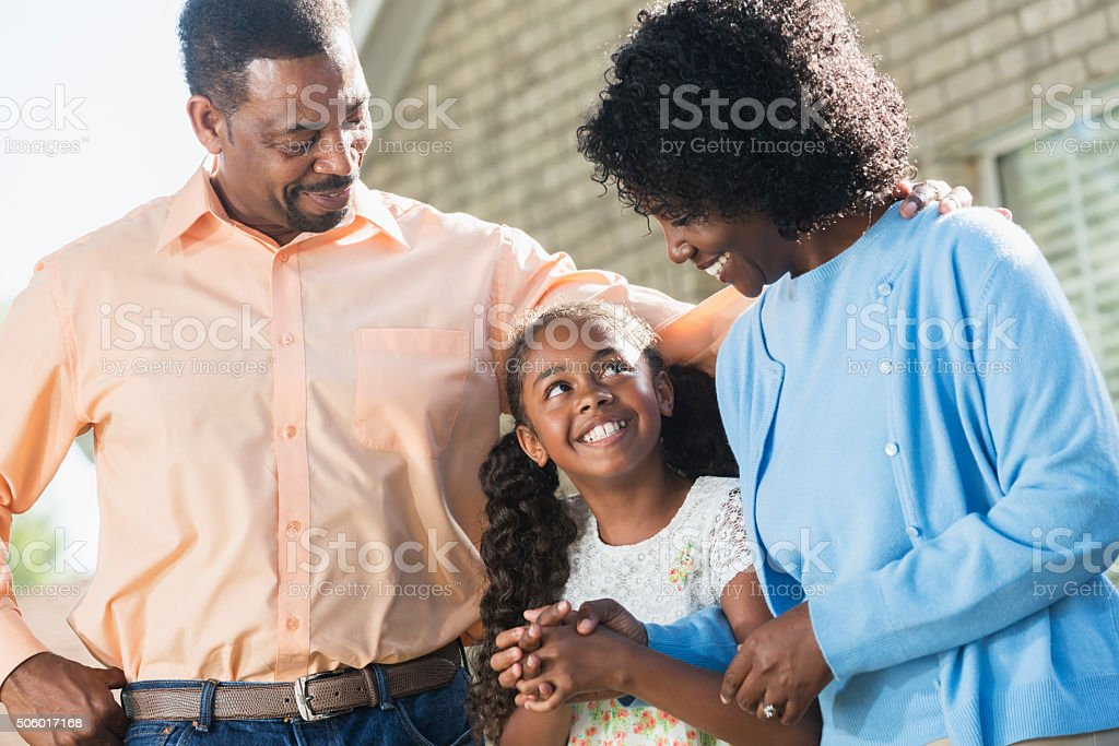African American girl with parents in front of house stock photo
