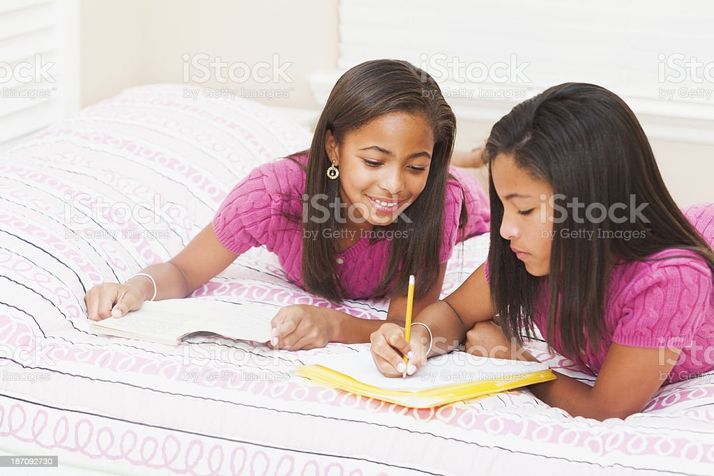 African American girls doing homework at home in bedroom stock photo