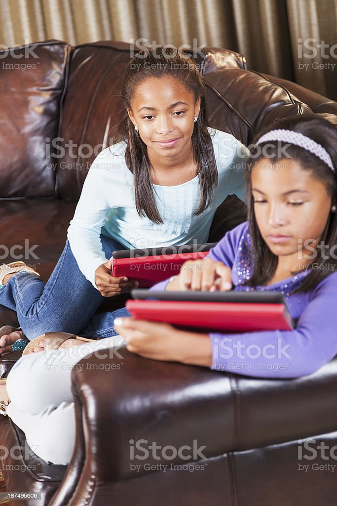 African American girls sitting on sofa using digital tablets stock photo