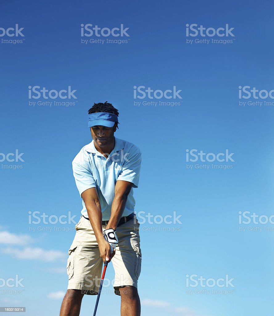 African American golfer about to shoot over the blue sky royalty-free stock photo