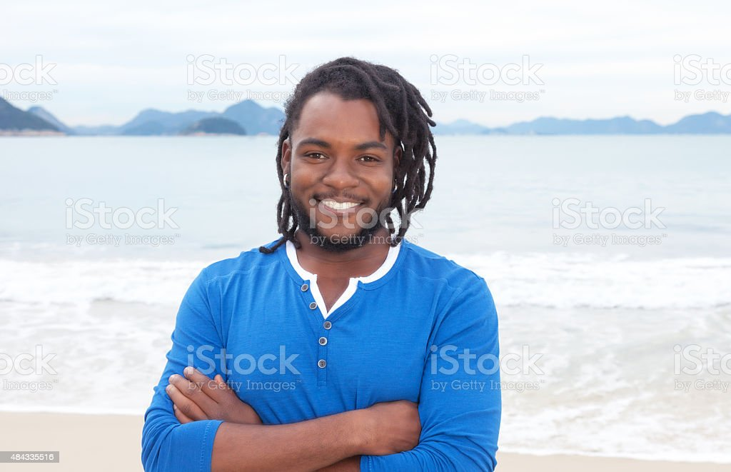African american guy with dreadlocks and crossed arms at beach stock photo