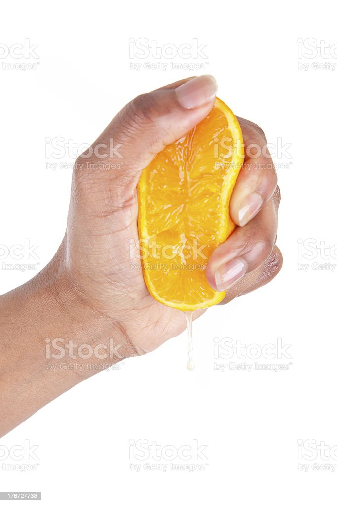African American hand squeezing an orange slice stock photo