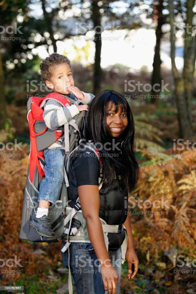 African American Hiker Carrying Toddler On Her Back royalty-free stock photo