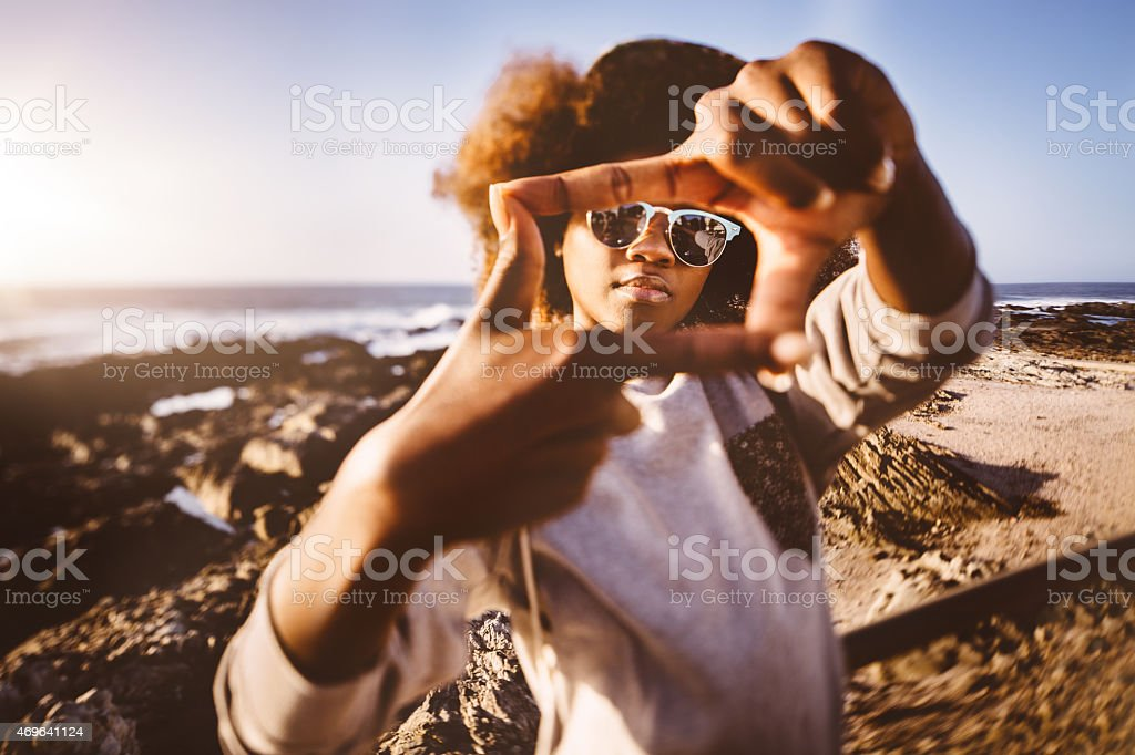 African American hipster teen at beach making frame with fingers stock photo