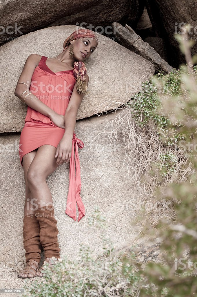 African American Jamaican woman leaning on rock stock photo