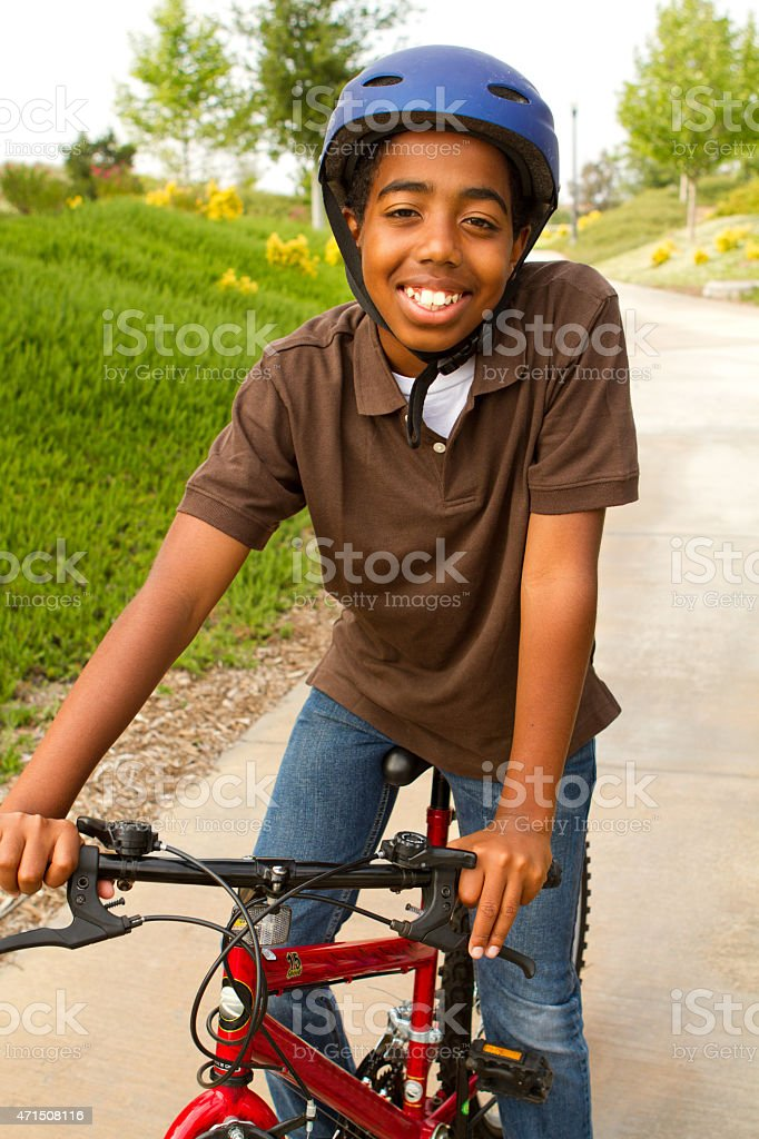African American kid riding a bike. stock photo