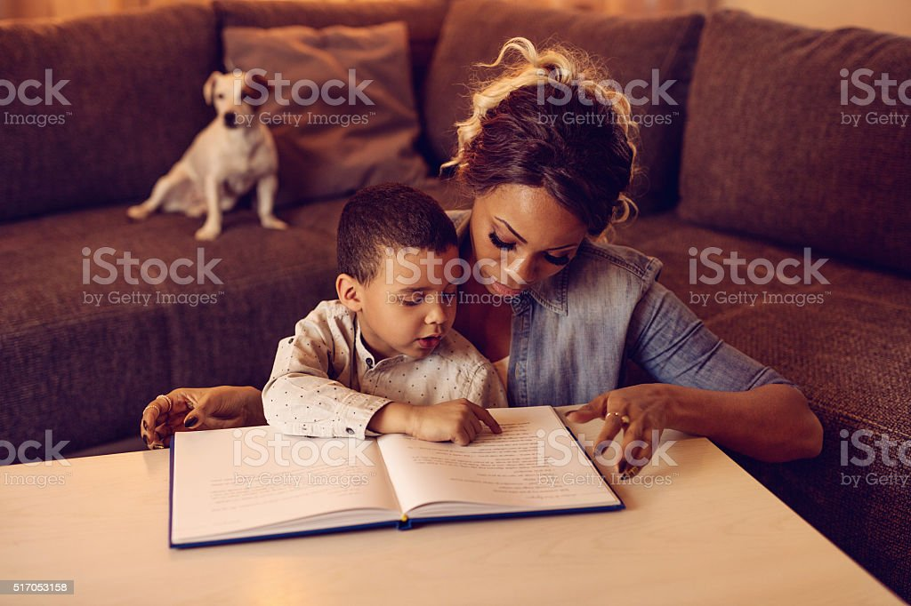 African American little boy and his mother reading a story. stock photo