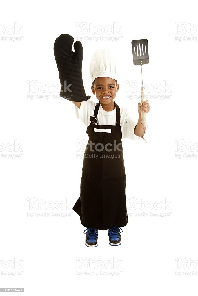 African American Little Boy Plays Chef Holding Barbecue Cooking Utensils stock photo