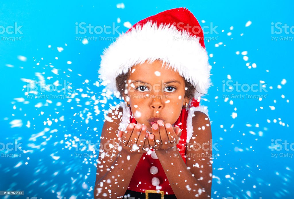 African American little girl in Santa Claus hat blowing snowflakes stock photo