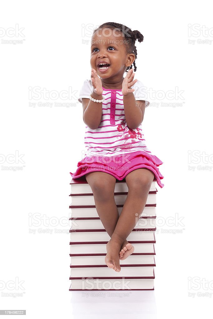 African american little girl seated in a stack of books stock photo