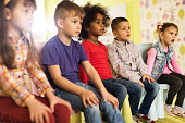 African American little girl sitting at preschool with her friends.