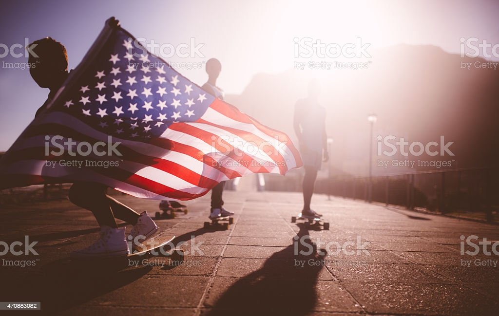 African American longboarder flying an American flag stock photo