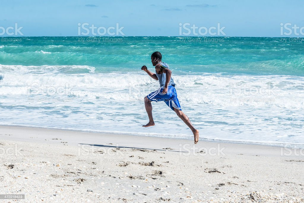 African American Male Running on Vero Beach stock photo