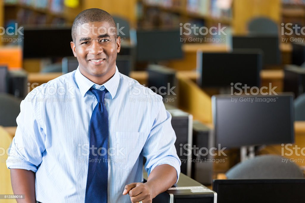 African American male teacher standing in computer lab stock photo