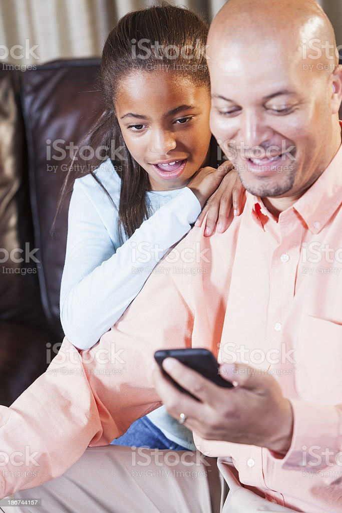 African American man and daughter looking at smartphone stock photo