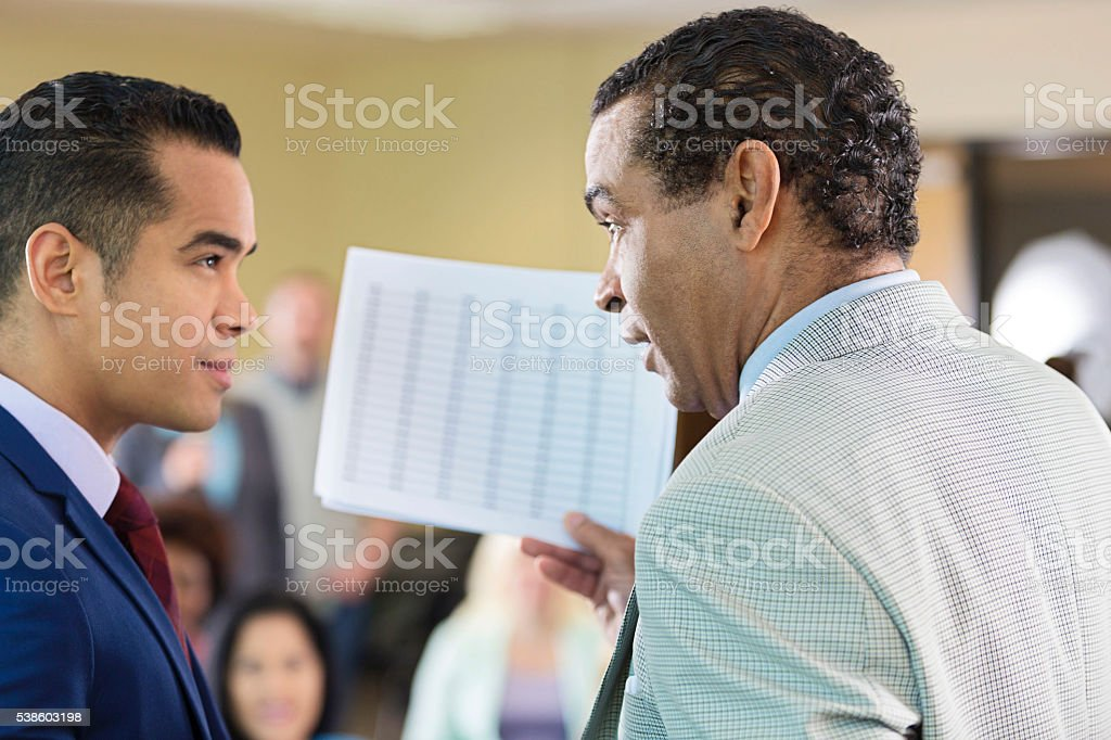 African American man and Hispanic man discuss papework stock photo